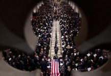 ・・・ The flag-draped casket of former President George H.W. Bush is carried out...